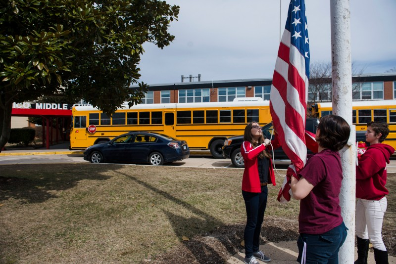 Meghan Meza,from left, Meghan Jones, middle and Summer Gilliard, lower the flag at Quantico Middle/High School on March 13, 2015 in Quantico, VA.