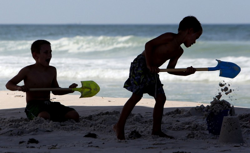 In this Monday, June 15, 2015, file photo, kids build a sand castle beneath the M.B. Miller County Pier in Panama City Beach, Fla.