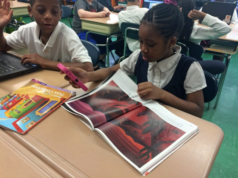 Amy, a fourth-grader at P.S. 129, references the class's reading material before participating in a class Q&A on her cellphone.