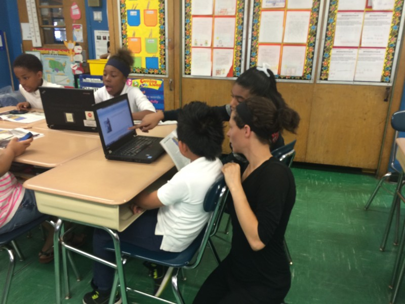Ryann Geldner, a special education teacher at P.S. 129, helps a student using a classroom laptop during a BYOD session.
