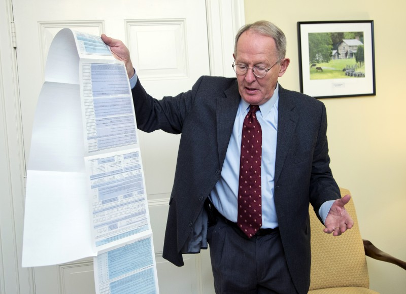 This Nov. 14, 2014, photo, shows Sen. Lamar Alexander, R-Tenn., holding the Free Application for Federal Student Aid (FAFSA) form, during an interview on Capitol Hill in Washington.