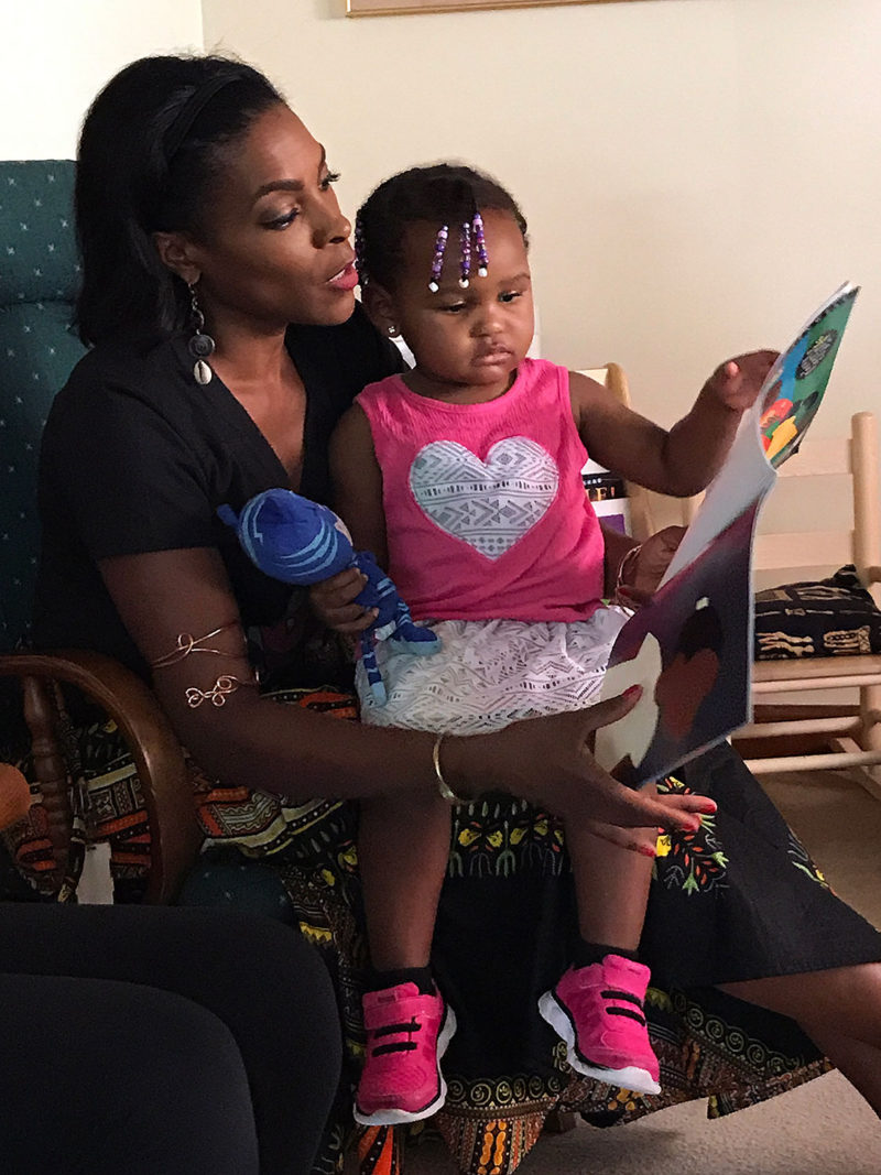 Seated in the living room of her home, Lorna Parks reads aloud to Maikko, 2. Parks runs a home-based child care program, called House of Joy, in Detroit.