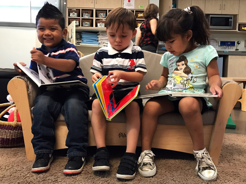 """Educare Arizona classmates Nathan Jaramillo, far left, Esteban Cuevas and Melissa Gordillo """"read"""" books during free time in their toddler classroom. Children begin learning basic literacy skills, like which direction to turn the pages, around age 2. Lillian Mongeau/The Hechinger Report"""