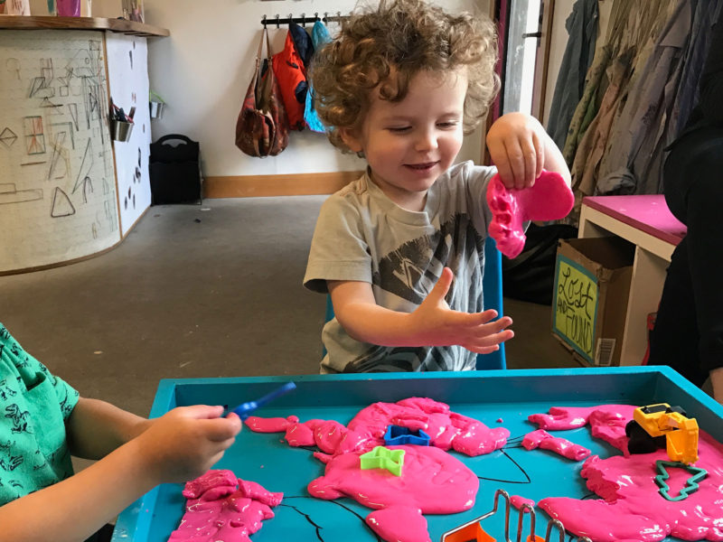"""Clark Tinker, age 2 in this photo, holds up some """"oobleck,"""" a concoction made out of cornstarch and water, at a play space in Portland, Ore. Sharing toys and other play materials is a tough task for 2-year-olds."""