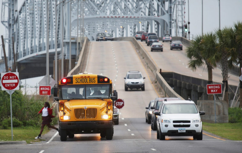 A school bus drops off a student in front of the Claiborne Bridge in the Lower Ninth Ward in New Orleans, Louisiana.