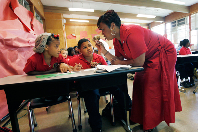 Trenise Duvernay talks to Miracle Lee, left, and Danny Dinet, center, as she teaches fourth grade math class at the Alice M. Harte Charter School in New Orleans.