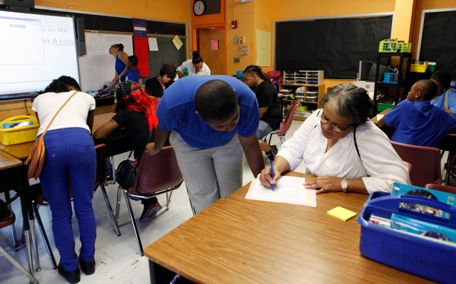 D'Andre walks back and forth between his grandmother, Jean (front), and his mom and sister (rear) as they fill out parental contact information forms in his seventh-grade English class. (Amanda Brown / NJ Spotlight)
