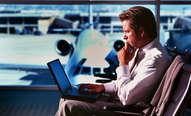 Businessman with Laptop in Airport