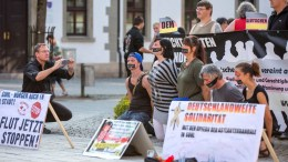 Right-wing demonstrators sit behind a placard that reads ''Germany-wide solidarity' on the market square in Suhl, Germany, 22 August 2015. A nationwide network of hooligans, neo-nazis and supporters of anti-Islam organisation Pegida had called for the third rally this week against Germany's refugee policy. EPA/MICHAEL REICHEL