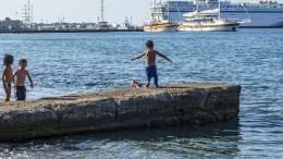 Φωτογραφία Αρχείου: Migrant children play at the beachfront at a makeshift camp site on the Greek island of Kos, Greece, 16 August 2015. The Greek island is struggling with a major influx of refugees and migrants amidst the financial crisis and the height of the tourist season. EPA/ODYSSEUS
