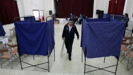 A man walks among empty polling booths for a leadership election of New Democracy party, in Athens, Greece, 22 November 2015. The planned election of a new party leader were postponed due to technical problems. The party's Central Electoral Committee in an extraordinary meeting decided unanimously to postpone the voting procedure. EPA, ALEXANDROS VLACHOS