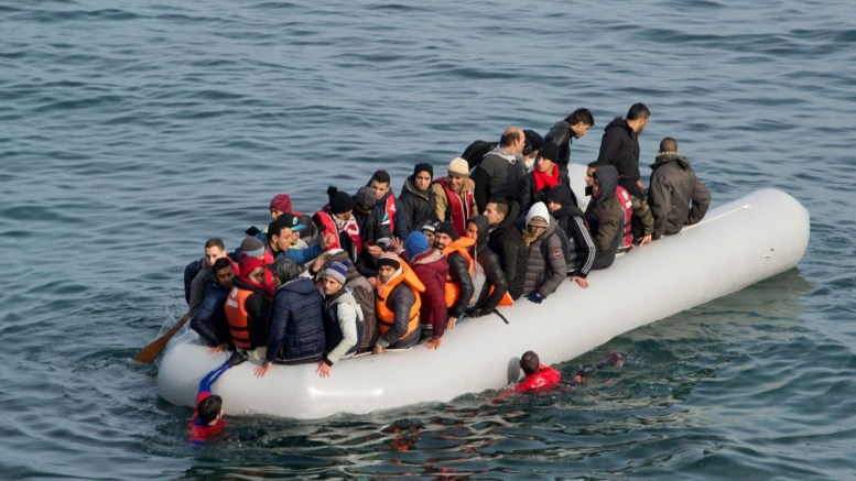 FILE PHOTO. Refugees and migrants arrive in an overloaded rubber dinghy. EPA, STRINGER