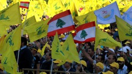 FILE PHOTO: Supporters of Hezbollah wave party flags as they listen to a televised speech by Hezbollah leader Hassan Nasrallah. EPA, LUCIE PARSAGHIAN