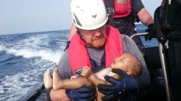 FILE PICTURE. A German rescuer from the humanitarian organisation Sea-Watch holds a drowned migrant baby, off the Libyan cost. Photo Christian Buettner, Eikon Nord GmbH Germany, Handout via Sea-Watch