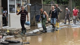 People with shovels walk through a flooded street in the village of Stajkovci, Skopje, The Former Yugoslav Republic of Macedonia on 07 August 2016. At least 15 people have died in a rain storm that hit the FYROMian capital Skopje late on 06 August 2016 causing severe damage to roads, houses and infrastructure. Around 80 vehicles were caught in landslides the hit Skopje's ringroad which remains closed. EPA, GEORGI LICOVSKI