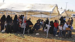 FILE PHOTO. Syrian refugees wait under a tent after crossing the border in Hatay province, Turkey. EPA, ISMIHAN OZGUVEN TURKEY OUT
