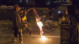A demonstrator drags a burning American flag through the streets during a march through the streets in protest against President-elect Donald Trump in Oakland, California, USA 10 November 2016. Hundreds filled the streets of downtown Oakland for the second night to march against the Trump presidency. EPA, PETER DASILVA