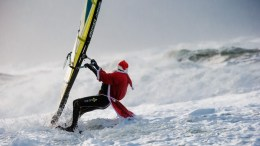 A windsurfer dressed as Santa Claus surfs on a windy day on the island of Sylt, Germany, 26 December 2016. EPA, MARKUS SCHOLZ