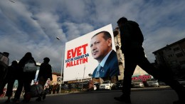 Turkish people walk in front of a giant picture of Turkish President Recep Tayyip Erdogan reading, 'Vote Yes, only public can speak and make decision', in Istanbul, Turkey. EPA, SEDAT SUNA