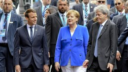 French President Emmanuel Macron (2-L), German Chancellor Angela Merkel (C) and Italian Prime Minister Paolo Gentiloni (R) are accompanied by security personnel as they walk off after the group photocall at on the firts day of the G7 Summit, in Taormina, Italy. EPA, CIRO FUSCO