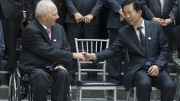 German Finance Minister Wolfgang Schauble (L) shakes hands with Minister of Finance of China Xiao Jie (R) at the International Monetary Fund (IMF) headquarters in Washington, DC, USA. EPA, MICHAEL REYNOLDS