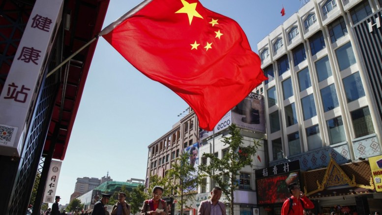 FILE PHOTO. People walk past a China flag. EPA/ROLEX DELA PENA