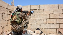 FILE PHOTO. A soldier aims an automatic rifle through a peephole in a wall at Raqqa city, Syria. EPA/YOUSSEF RABIE YOUSSEF