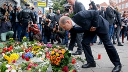 Hamburg Mayor Olaf Scholz (front) and Hamburg Interior Senator Andy Grote place flowers in front of a supermarket where a man attacked clients the day before in Hamburg, Germany, 29 July 2017. One victim is reported dead and seven were injured. The arrested attacker of Arabic descent was subject to a final deportation order, is suspected to have an Islamist background and is classified as mentally instable, Hamburg Interior Senator announced 29 July 2017. EPA, MARIUS ROEER