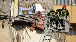Firefighters work amid the rubble of a building that collapsed in Torre Annunziata, near Naples, southern Italy. According to news reports, up to eight people are believed to be trapped in the rubble. EPA/CIRO FUSCO.