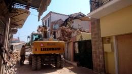 Συνεργεία του δήμου γκρεμίζουν κτίσματα που έχουν υποστεί ζημίες από τον σεισμό της 12ης Ιουλίου, στο χωριό Βρίσα Μυτιλήνης. ΑΠΕ-ΜΠΕ/ΣΤΡΑΤΗΣ ΜΠΑΛΑΣΚΑΣ.