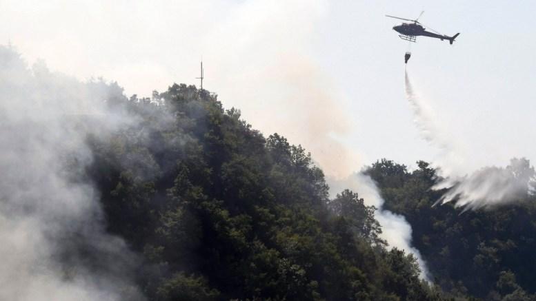 A helicopter spreads water over an area of a forest fire in Dajti Mountain in Tirana, Albania. EPA, MALTON DIBRA