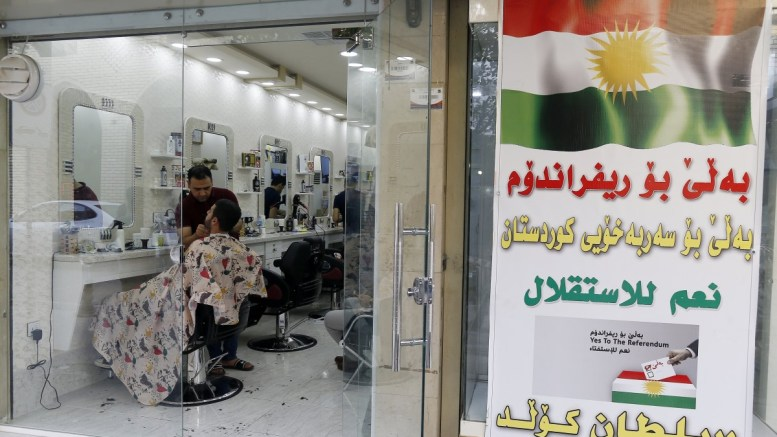A poster for the referendum calling on Kurds to vote for independence is seen on the wall next to a hairdresser's shop in the old city of Erbil, Kurdistan region in northern Iraq, 26 September 2017. Reports state that around 72 percent of the roughly five million eligible voters participated in the Iraqi Kurdistan independence referendum on 25 September. EPA, MOHAMED MESSARA