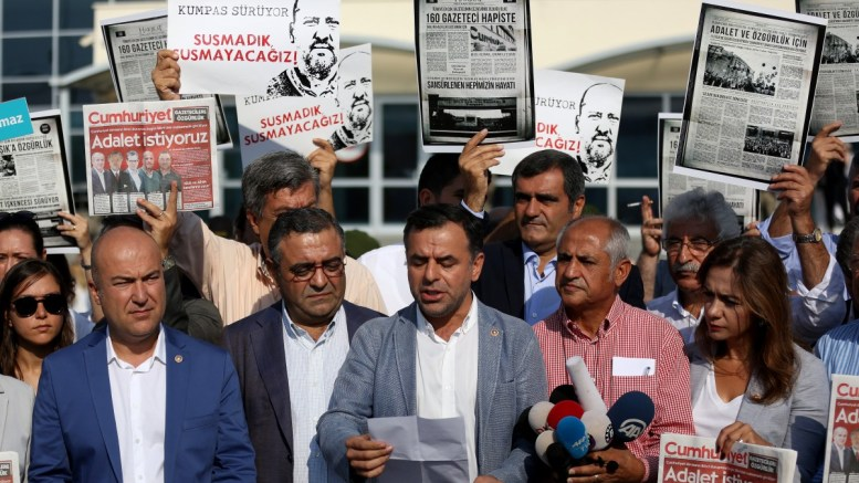File Photo: People hold copies of the current Cumhuriyet newspaper's edition and picture of journalists on trial in front of the Silivri Prison during a trial against staff of Cumhuriyet newspaper in Istanbul, Turkey, 11 September 2017. A trial against a total of 17 current and former Cumhuriyet writers, cartoonists and executives who on charges releated to terror resumes at the prison on 11 September.  EPA, ERDEM SAHIN