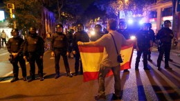File Photo: A protester opposing the unilateral declaration of independence holds a Spanish national flag in front of police officers on a street in Barcelona, Catalonia, Spain. EPA, ALBERTO ESTEVEZ