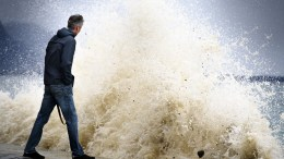 A man watching waves pounding the lakeside promenade on the Lake of Geneva, in Vevey, Switzerland, 03 January 2018. The Storm Burglind is cause strong gusts of wind of up to 200 kilometres an hour in some mountain areas.  EPA/LAURENT GILLIERON