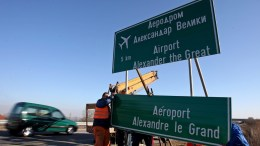 FILE PHOTO. Workers fix a road sign with the name of Skopjes airport 'Alexander the Great' with English and French transcription. EPA, GEORGI LICOVSKI