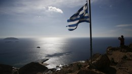 A Greek national flag flutters as Flora Chalari, 52, takes a picture of the Greek Navy warship 'Prometheus' from the top of the capital of Anafi, during a mission of military medical staff organised by the Hellenic Navy, on the Greek island of Anafi in the Aegean sea, Greece.  EPA, YANNIS KOLESIDIS