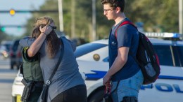 A woman is comforted by a police officer after a shooting at Marjory Stoneman Douglas High School in Parkland, Florida, USA, 14 February 2018. EPA, GIORGIO VIERA
