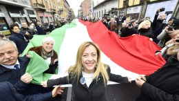 Giorgia Meloni (C), leader of the national conservative party Fratelli d'Italia (FdI, Brothers of Italy) walks in front of a giant Italian flag during a rally staged by the FdI in Milan, Italy, 24 February 2018. Italy will hold general election on 04 March. EPA, FLAVIO LO SCALZO
