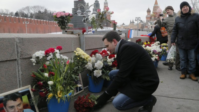 Russian opposition activist Ilya Yashin (C) lays flowers at the site of murder of opposition politician Boris Nemtsov, to mark the third anniversary of his murder in Moscow, Russia, 25 February 2018. EPA, MAXIM SHIPENKOV