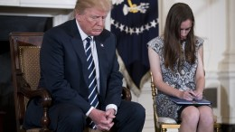 US President Donald J. Trump, with Marjory Stoneman Douglas High School student Carson Abt, bows his head prior to remarks during a listening session with high school students and teachers in the State Dining Room of the White House in Washington, DC, USA, 21 February 2018. EPA, SHAWN THEW