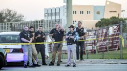 A group of police officers stand guard in front of the side entrance of the Marjory Stoneman Douglas High School after a shooting in Parkland, Florida, USA, 14 February 2018. EPA, CRISTOBAL HERRERA