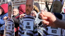 Albanian opposition supporters hold hand cuffs and puppets of Albanian Prime Minister Edi Rama, drug trafficants and former lawmakers during a protest in Tirana, Albania. EPA, MALTON DIBRA