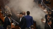 Kosovo lawmakers stand amid tear gas after canisters were released by opposition lawmakers before the vote for agreement on border demarcation with Montenegro during a parliamentary session in Pristina, Kosovo, 21 March 2018. EPA, VALDRIN XHEMAJ