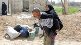 File Photo: A Syrian man carries his mother as hundreds leave rebels-held Eastern Ghouta in the countryside of Damascus, Syria, 15 March 2018. EPA, YOUSSEF BADAWI