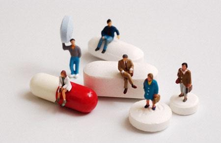 AM69E7  Group of tiny figures standing on sitting on and holding a variety of pills and capsules