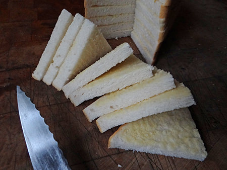 Slicing buttered slices of bread into triangles