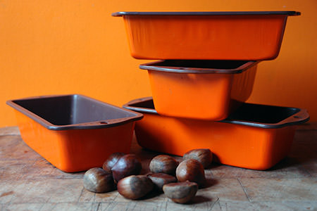 stack of orange cake tins and handful of chestnuts