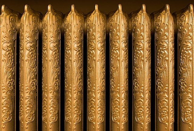 Detail of gold coloured cast iron radiator