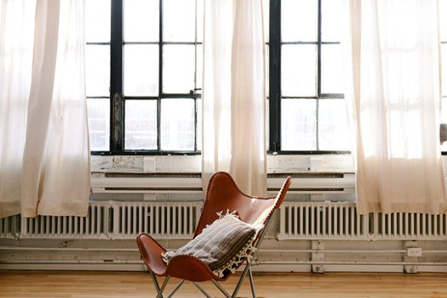 Industrial loft apartment with wall of under-window radiators